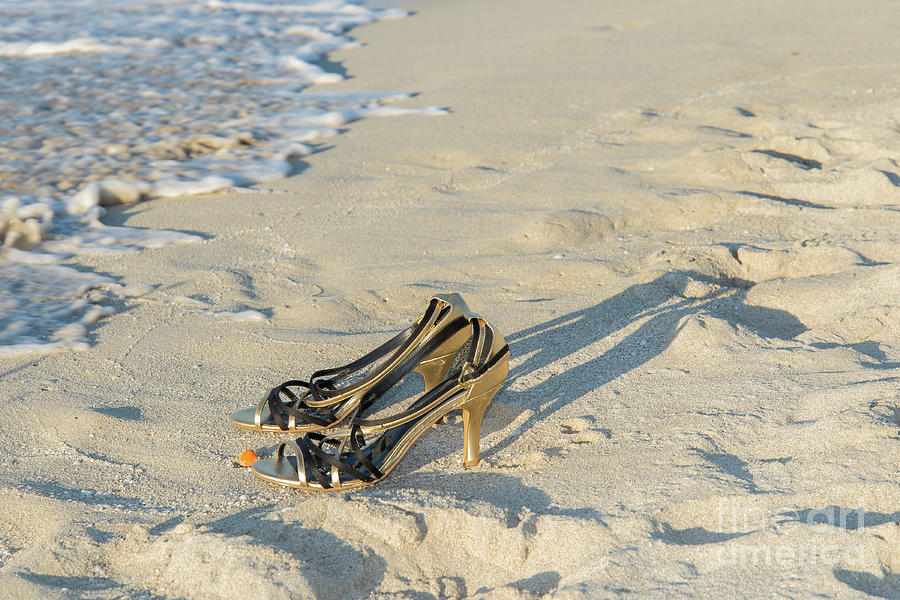 Golden high heel shoes on the beach by Les Palenik
