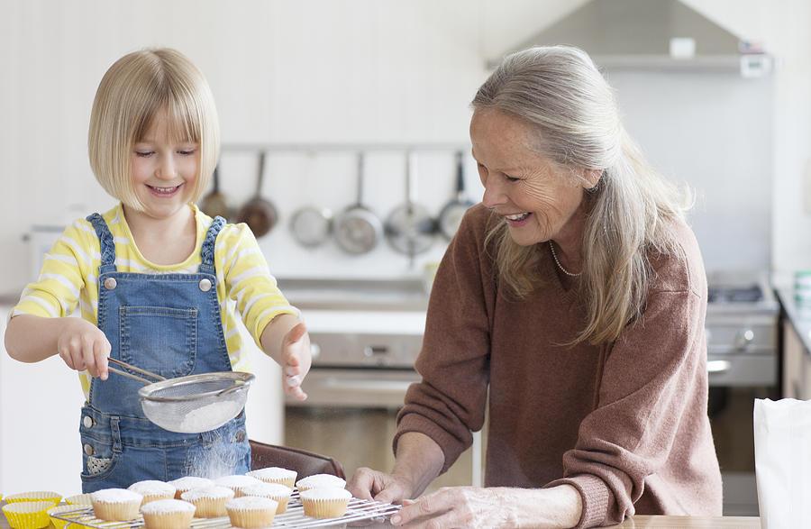 Granddaughter and grandmother baking cakes Photograph by Compassionate Eye Foundation/Natasha Alipour Faridani
