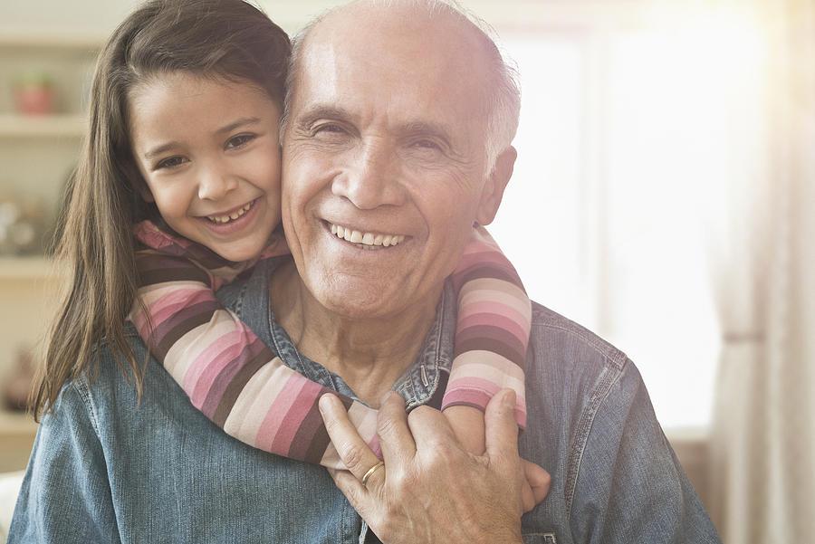 Granddaughter hugging grandfather Photograph by Jose Luis Pelaez Inc