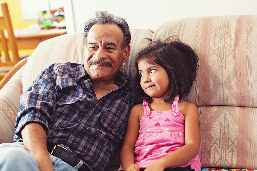 Grandfather and Granddaughter Laughing on Couch Photograph by Laura Olivas