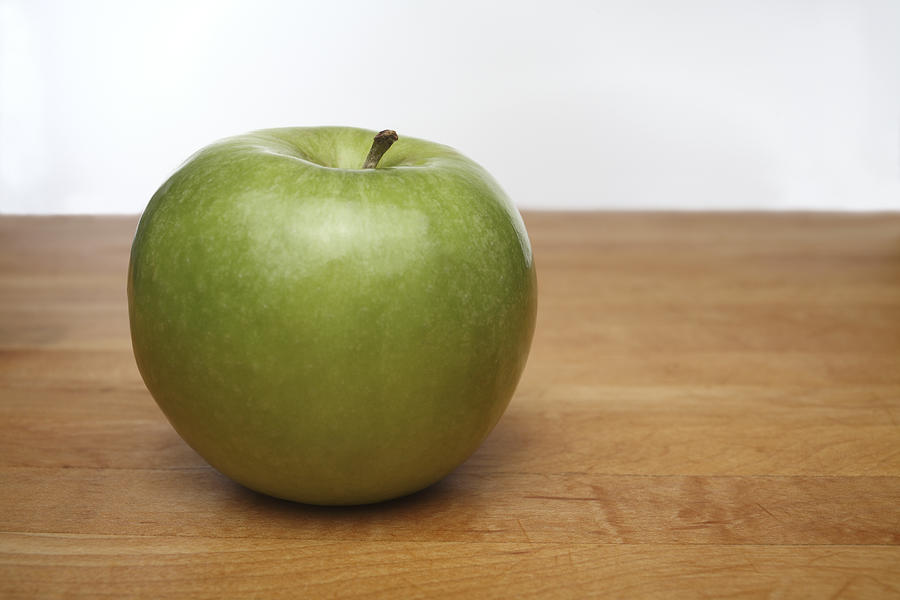 Green apple on wooden cutting board Photograph by Thomas J Peterson