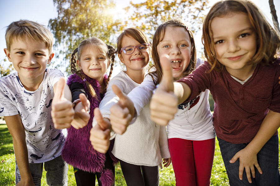 Group of children giving thumbs up Photograph by Damircudic