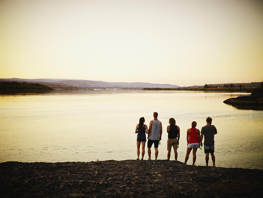 Group of friends looking out over river at sunset Photograph by Thomas Barwick