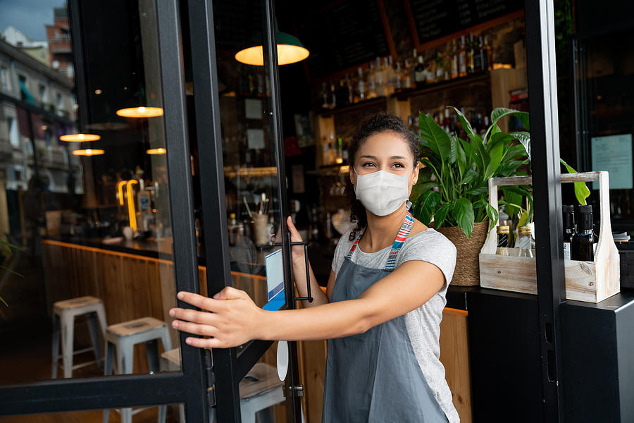 Happy business owner opening the door at a cafe wearing a facemask Photograph by Andresr
