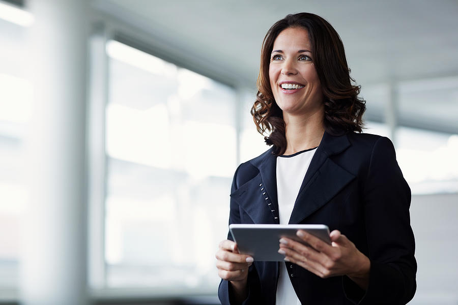 Happy businesswoman holding digital tablet Photograph by Morsa Images