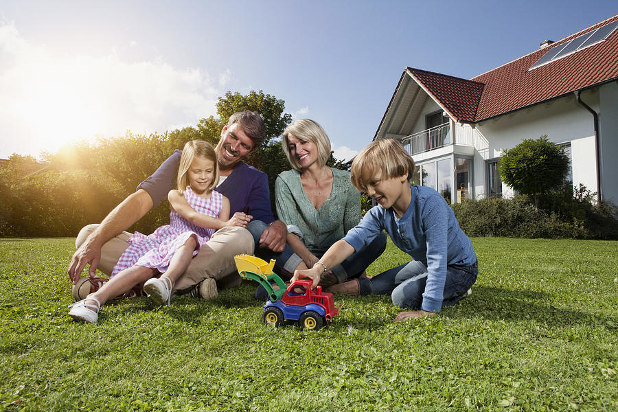 Happy family sitting on lawn in garden Photograph by Westend61