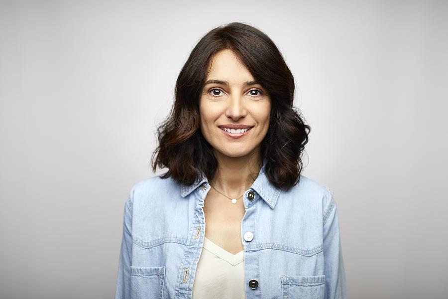 Happy female brunette CEO wearing blue denim shirt Photograph by Morsa Images