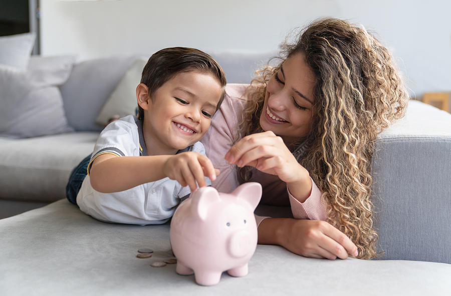 Happy mother and son saving money in a piggybank Photograph by Andresr