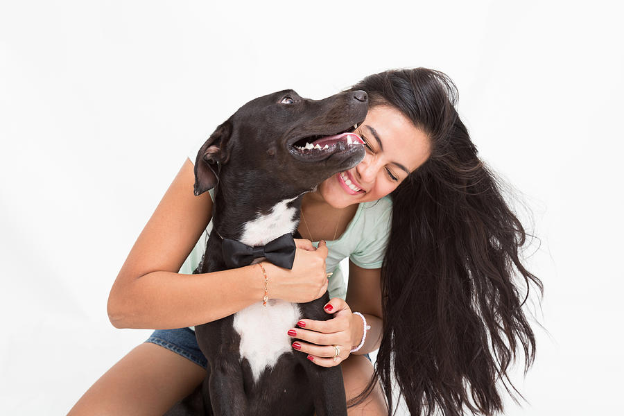 Happy Woman Playing With Dog Against White Background Photograph by Miguel Bandala / EyeEm