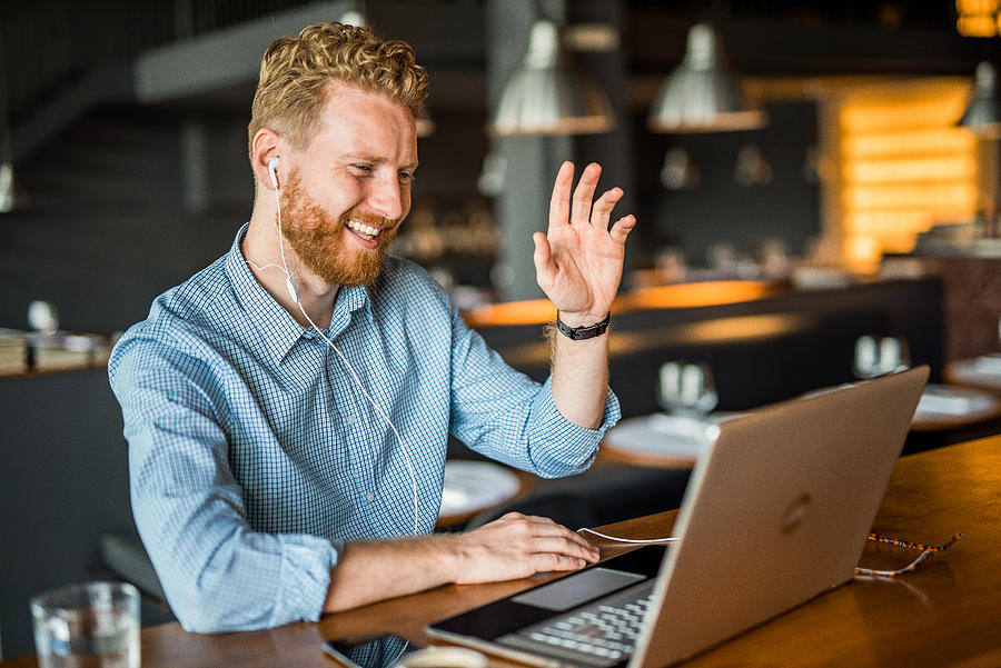 Happy young businessman waving to an online client. Photograph by DjelicS
