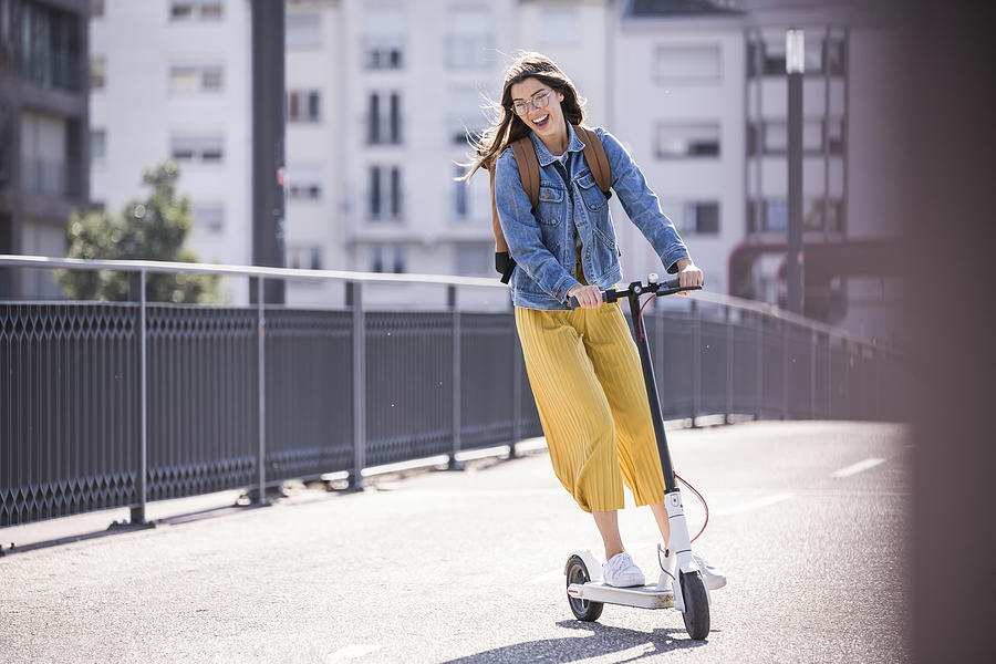Happy young woman riding electric scooter on a bridge Photograph by Westend61