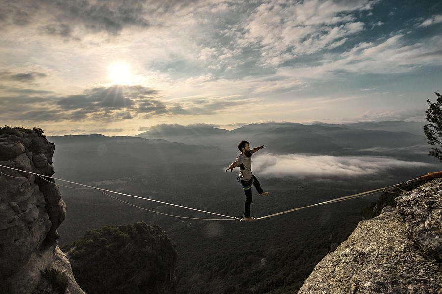 Highlining in the mountains at sunrise Photograph by Aluxum
