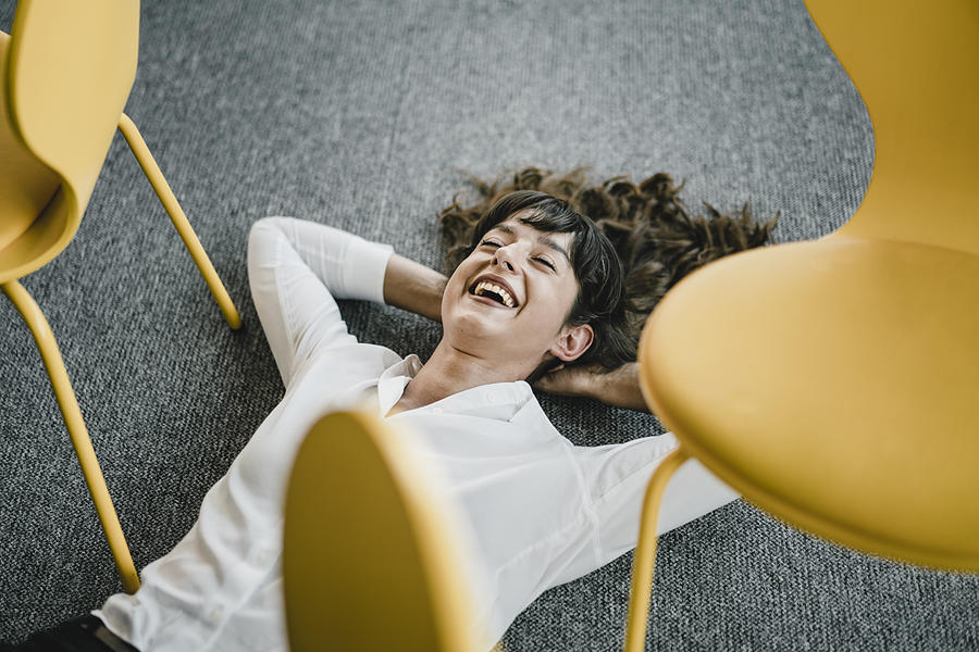 Laughing businesswoman laying in an office on the floor between chairs Photograph by Westend61