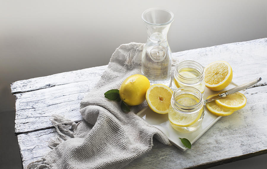 Lemon water on white wooden table. Still life. Photograph by Twomeows