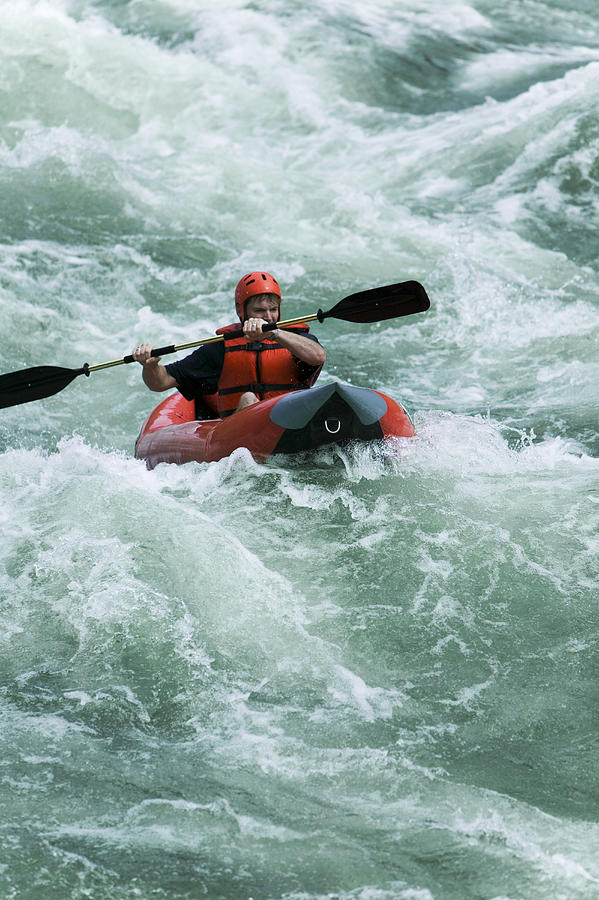 Lifestyle Shot Of A Young Adult Male As He Rides A Kayak Down Some River Rapids Photograph by Photodisc