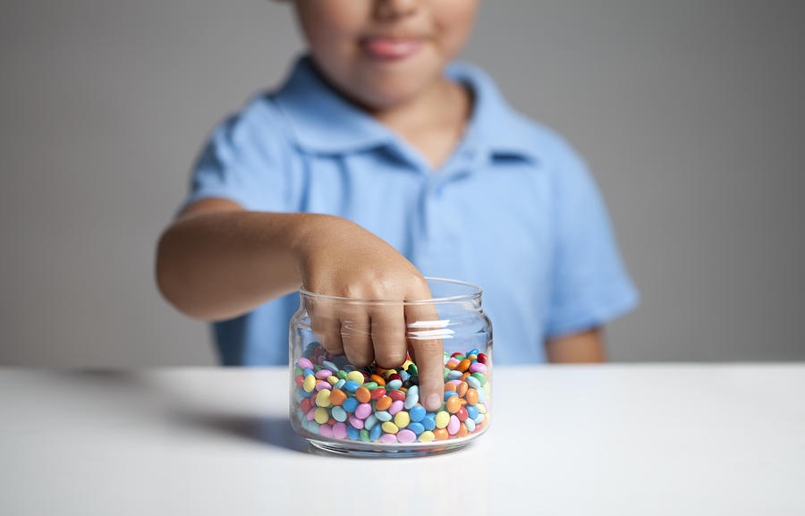 Little boy taking candy from jar Photograph by MarsBars