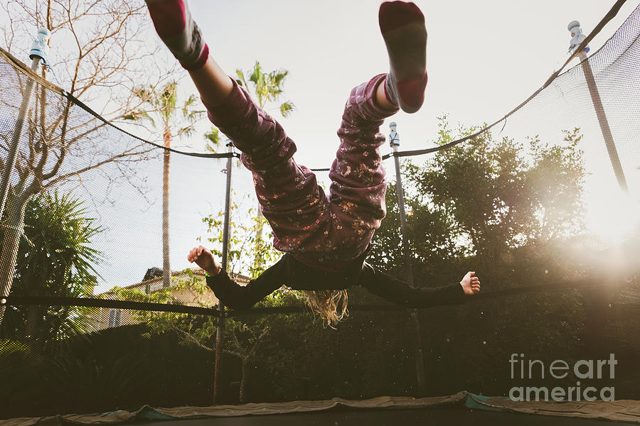 Little girl enjoying her vacation jumping on the trampoline doin by Joaquin Corbalan