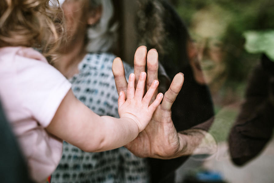 Little Girl Visits Grandparents Through Window Photograph by RyanJLane