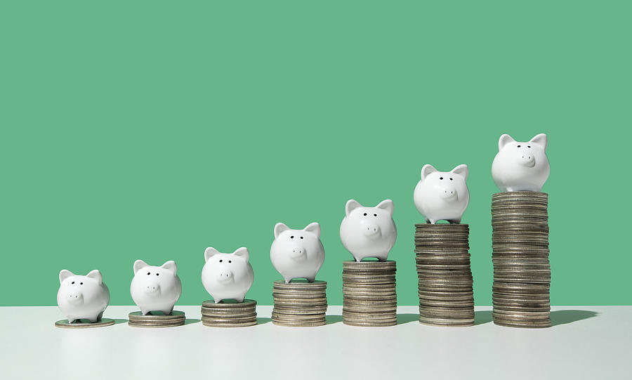 Little piggy banks on ascending stacks of coins Photograph by PM Images