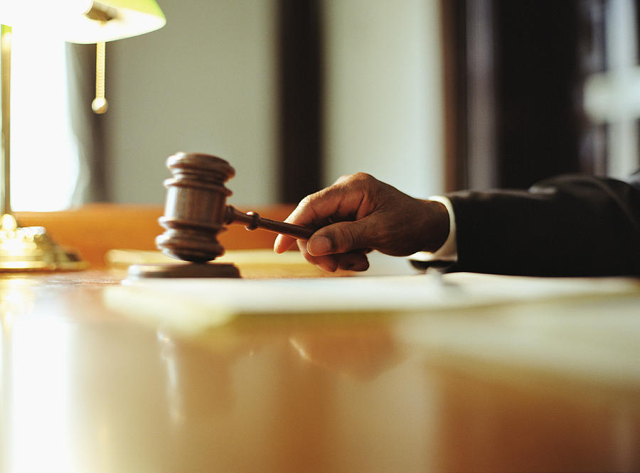 Male judge striking gavel in courtroom, close-up Photograph by Yellow Dog Productions