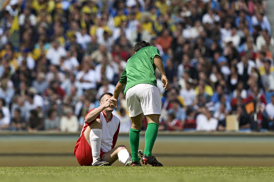 Male soccer player assisting opponent after tackle, in stadium Photograph by Photo and Co