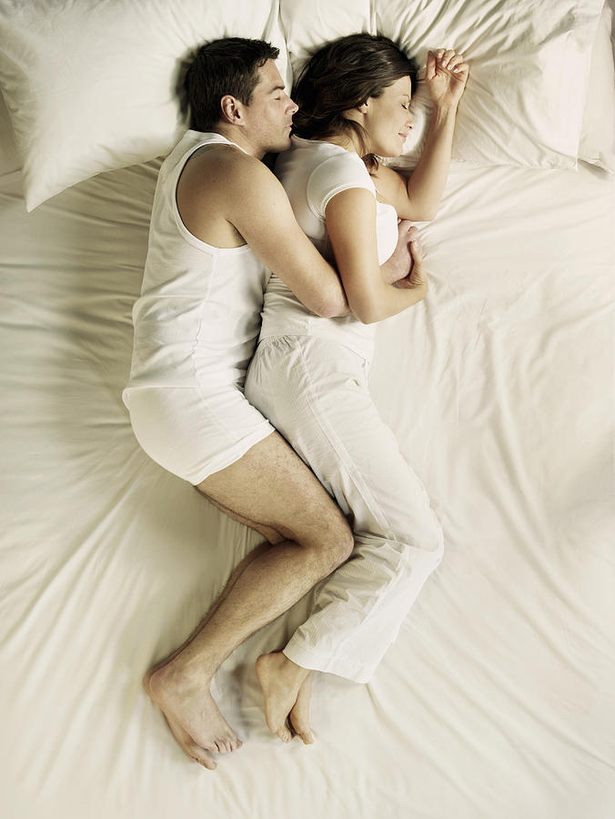 Man and woman cuddling in bed Photograph by Flashpop