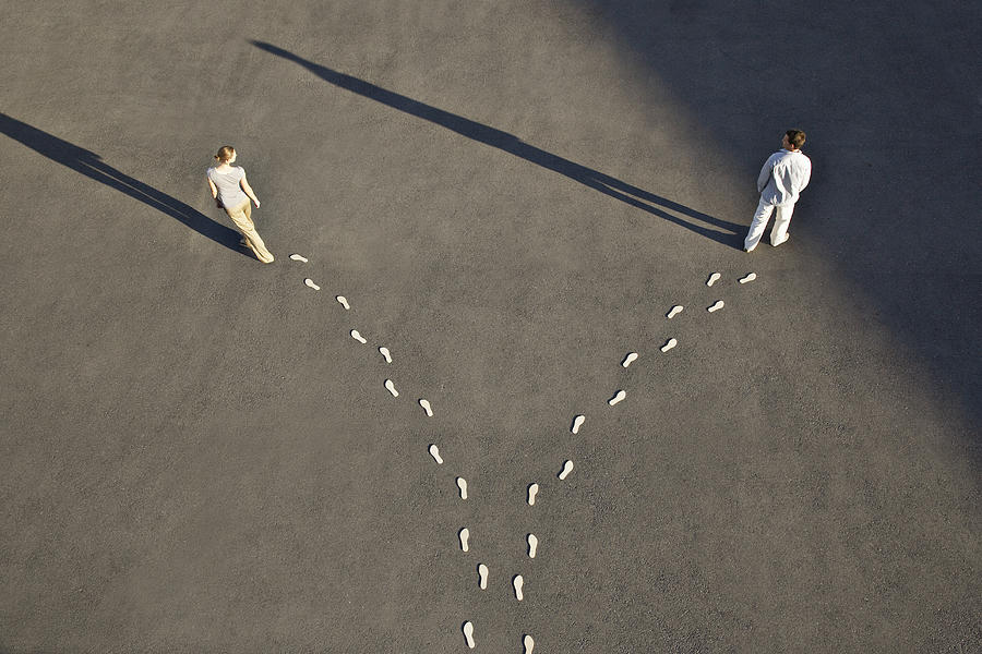 Man and woman with diverging line of footprints Photograph by Martin Barraud