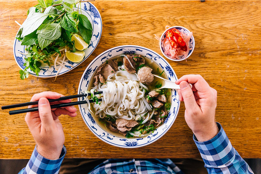 Man eating Vietnamese Pho soup with noodles and beef, personal perspective view Photograph by Alexander Spatari