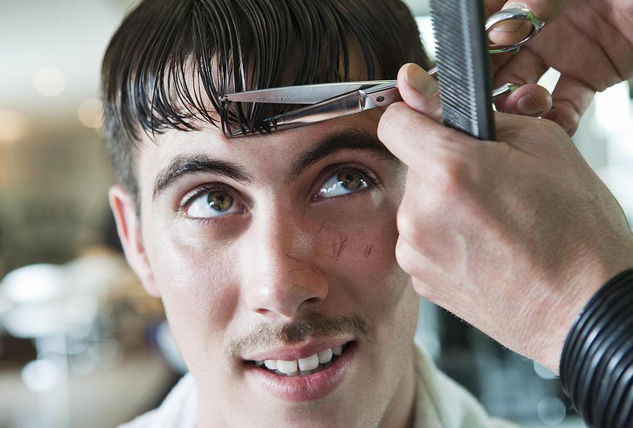 Man having his fringe cut by hairdresser Photograph by Dimitri Otis