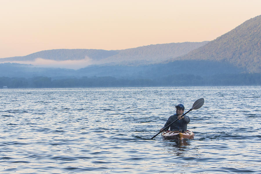 Man kayaking at sunrise on Skaneateles Lake, Skaneateles, New York State, USA Photograph by Ben Girardi / Aurora Photos