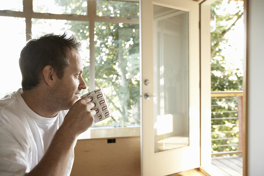 Man sitting indoors, drinking cup of coffee, side view Photograph by Thomas Northcut