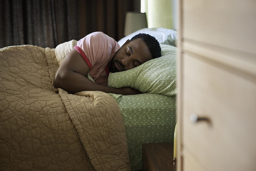 Man sleeping on bed at home Photograph by Cavan Images