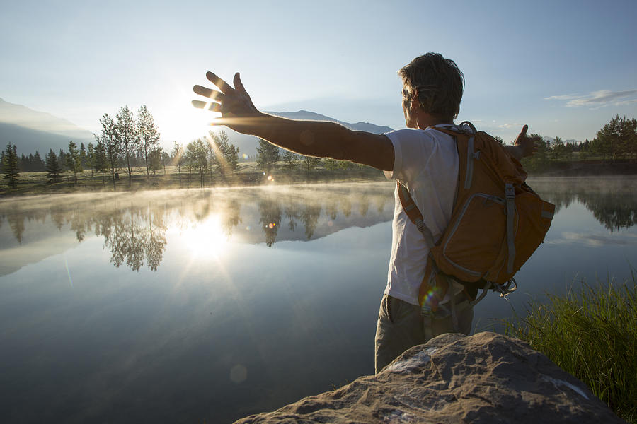 Man spreads arms wide across mountain lake Photograph by Ascent Xmedia
