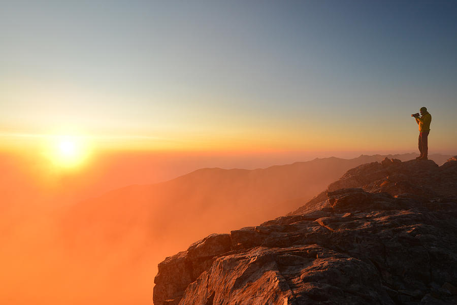 Man standing on top of a mountain at sunrise Photograph by Maya Karkalicheva