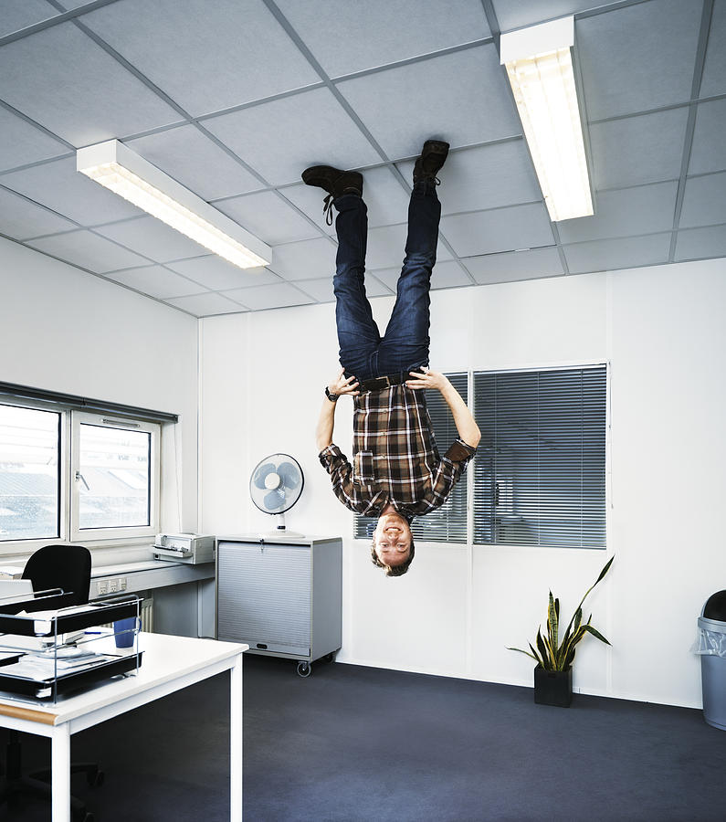 Man standing upside down on the ceiling. Photograph by Henrik Sorensen
