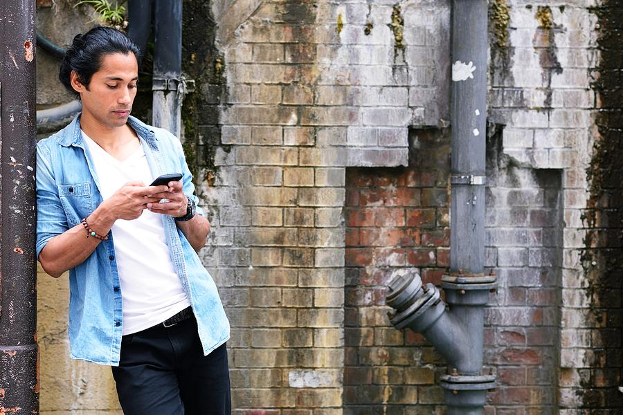 Man using a phone Photograph by Electravk