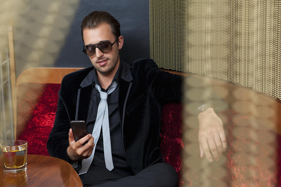 Man using cell phone in bar Photograph by Judith Haeusler