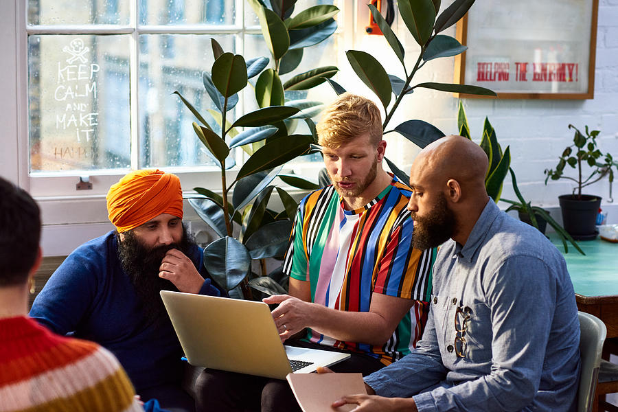 Man using laptop with multi racial colleagues Photograph by 10000 Hours
