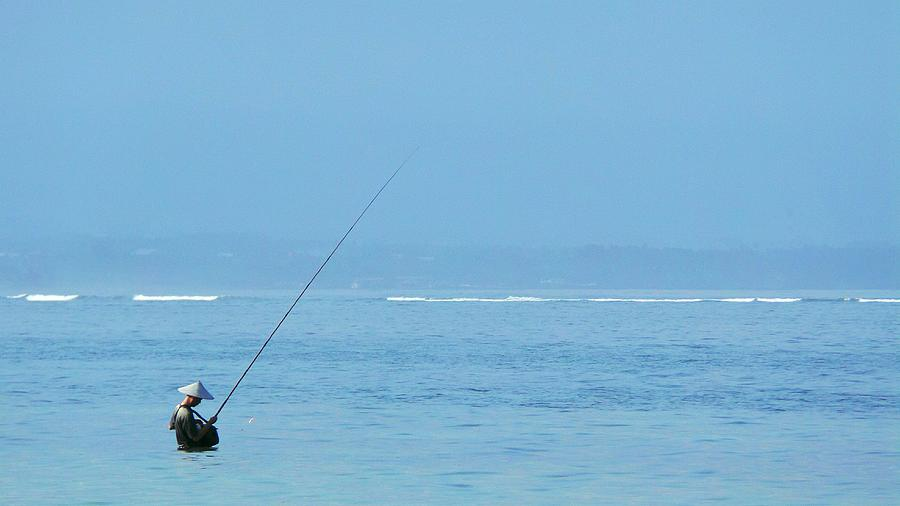 Man Wearing Asian Style Conical Hat While Fishing In Sea Against Sky Photograph by Joseph Jeanmart / EyeEm