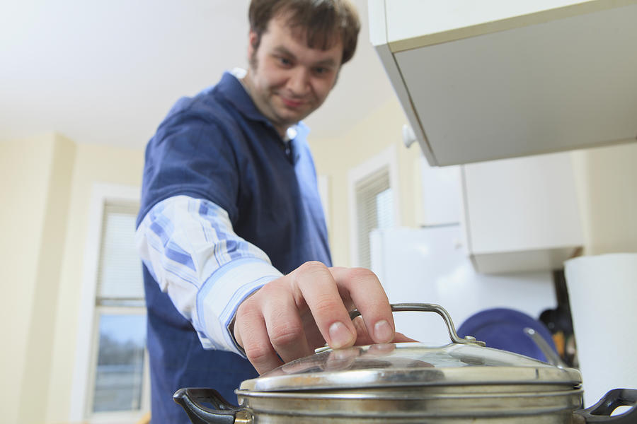Man with Aspergers living in his home and cooking Photograph by Huntstock