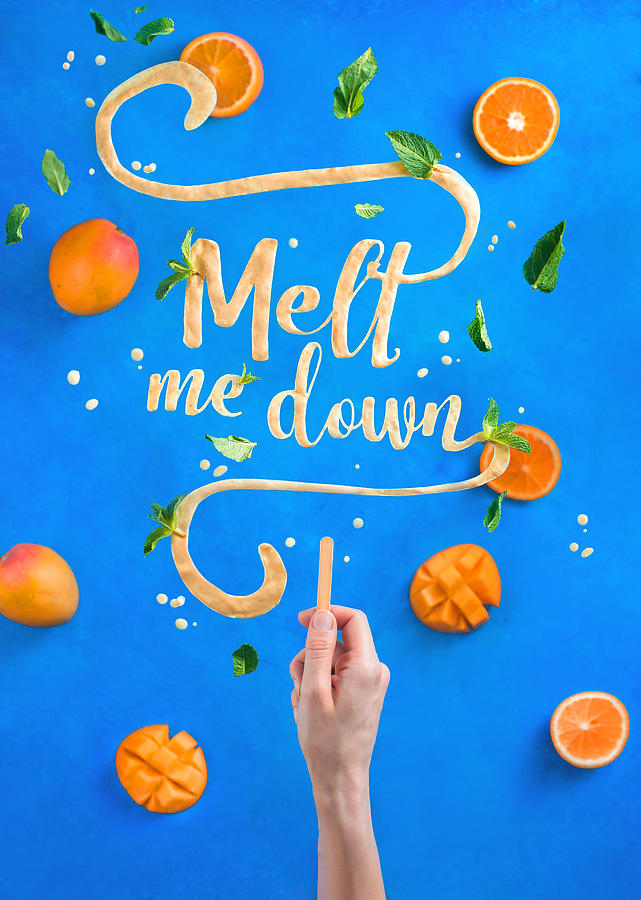 Mango ice cream lettering with popsicle stick spelling Melt Me Down. Creative fruit flat lay with a contrast blue background Photograph by Dina Belenko Photography