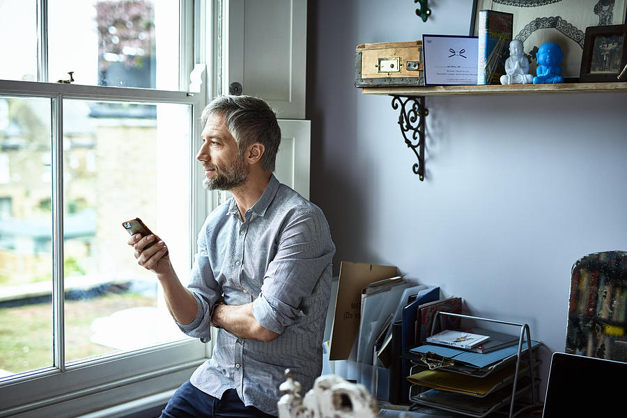 Mature businessman using phone in home office looking through window Photograph by 10000 Hours