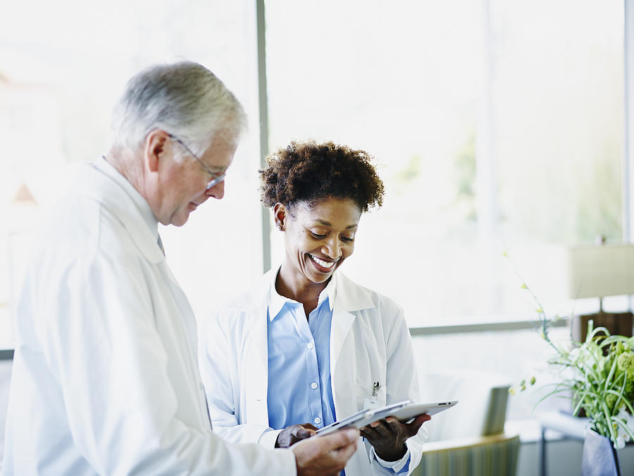 Mature doctors comparing notes on digital tablets Photograph by Thomas Barwick