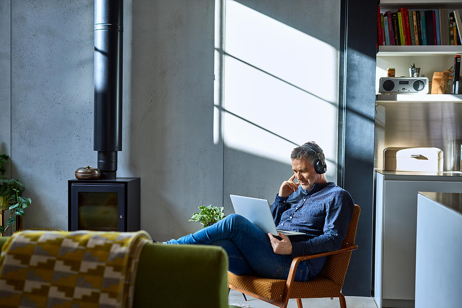 Mature man listening to music on laptop Photograph by 10000 Hours