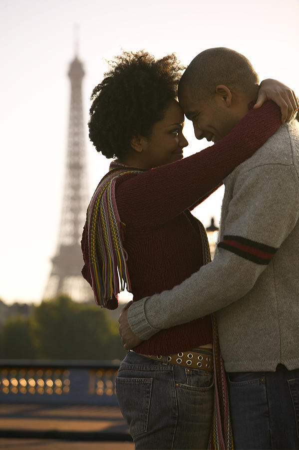 Medium Shot Of A Young Adult Couple As They Embrace At The Eiffel Tower In Paris Photograph by Photodisc