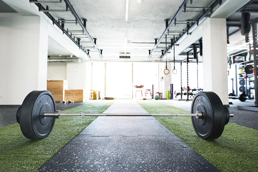 Metal heavy barbell laid on the floor in modern gym. Photograph by GrapeImages