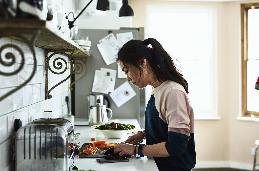 Mid adult Korean woman chopping vegetables on kitchen counter Photograph by 10000 Hours