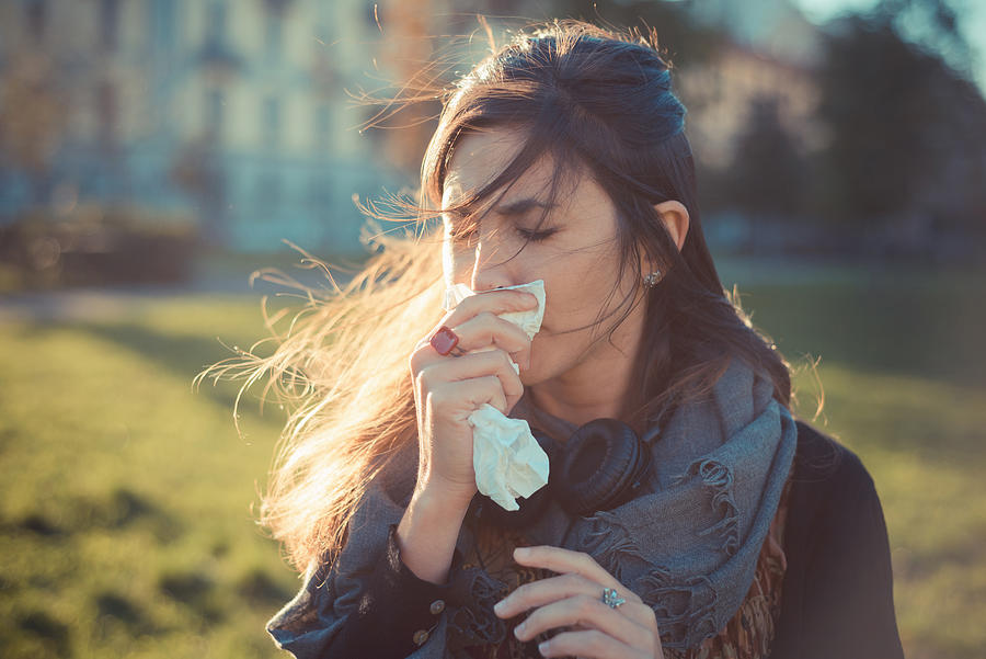 Mid adult woman blowing nose with hankerchief in park Photograph by Eugenio Marongiu