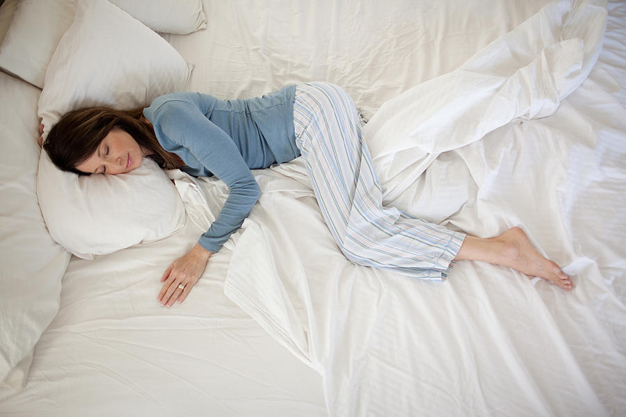 Middle Aged Woman Sleeping In Bed Photograph by Pete Barrett