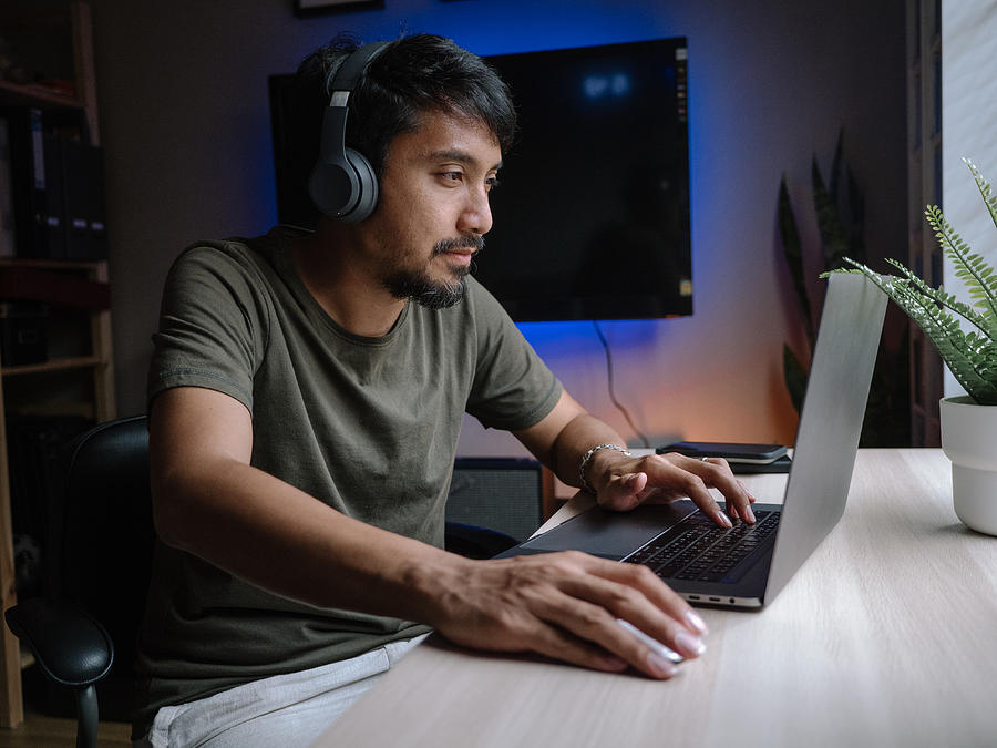 Millennial man playing computer game on laptop at home. Photograph by Staticnak1983